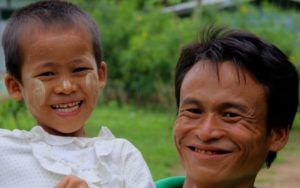 A happy father holds his daughter in Myanmar.