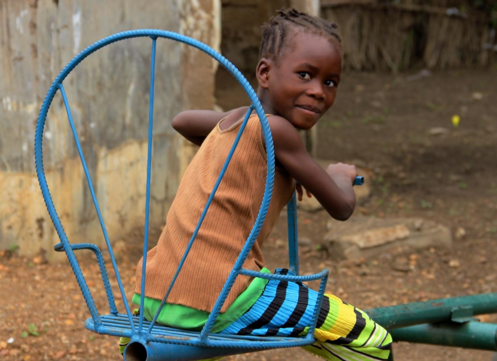 Young girl enjoys seesaw in Kenya.