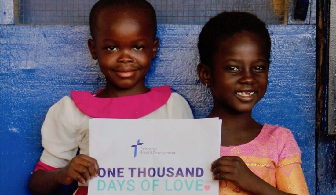 In Ghana, two young girls hold a ONE THOUSAND DAYS OF LOVE sign.