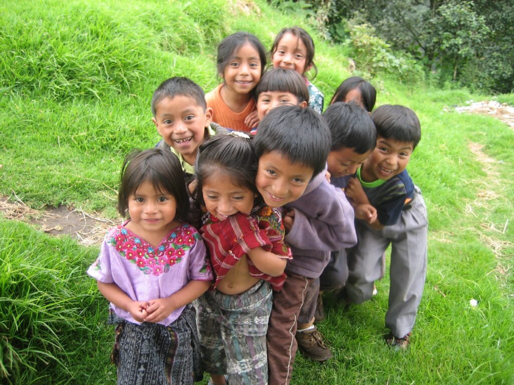 In Guatemala, a group of young children smile at the camera.