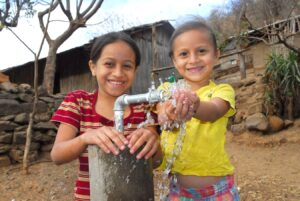 Two children stand next to an outdoor water faucet in Nicaragua. One rests her had on the pump. The other, in a yellow shirt, has her hands in running water.