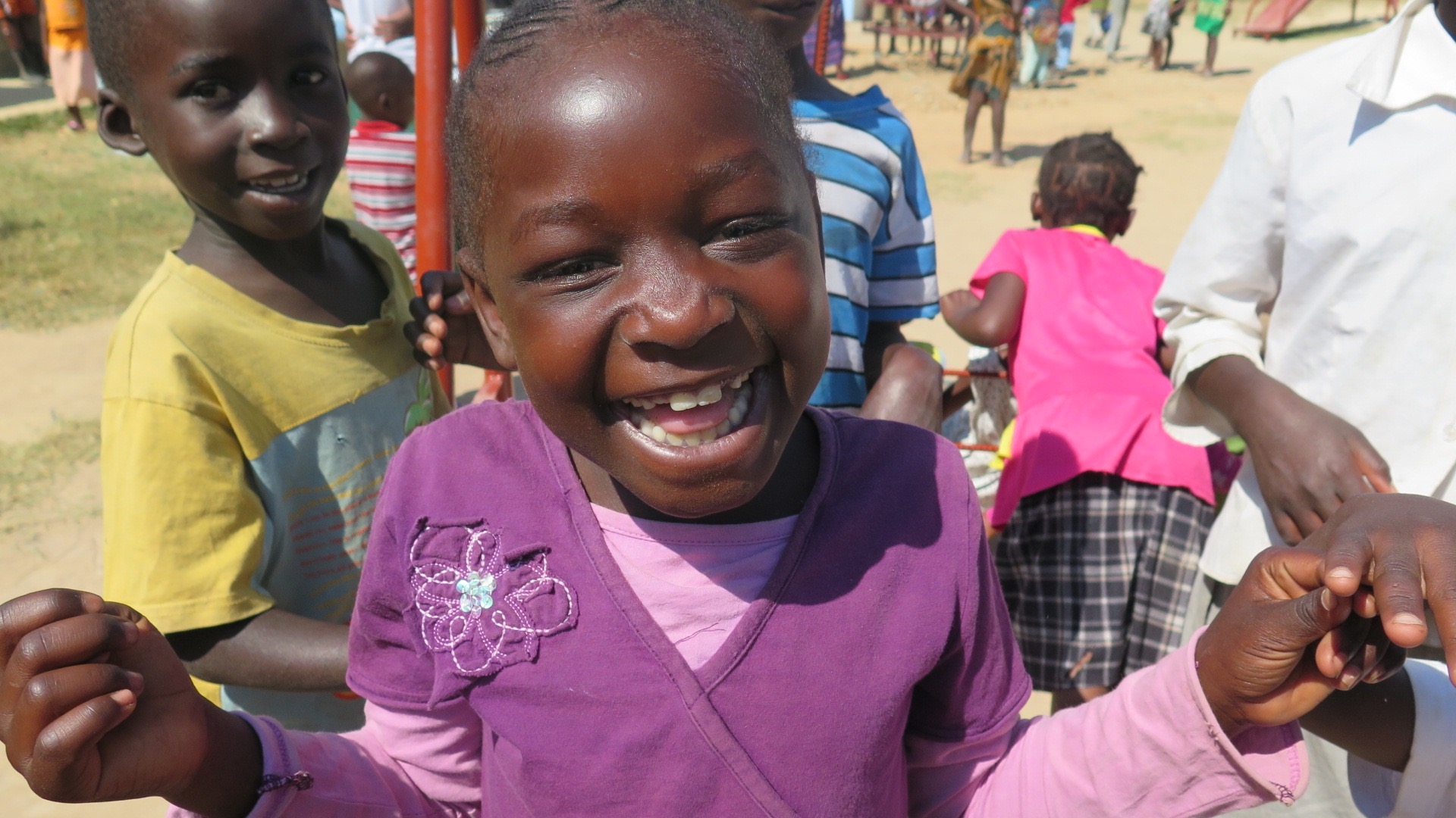 A young child in a purple sweater smiles in Zambia as others play behind her
