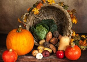 Basket with pumpkins, squash, tomatoes, and other seasonal vegetables
