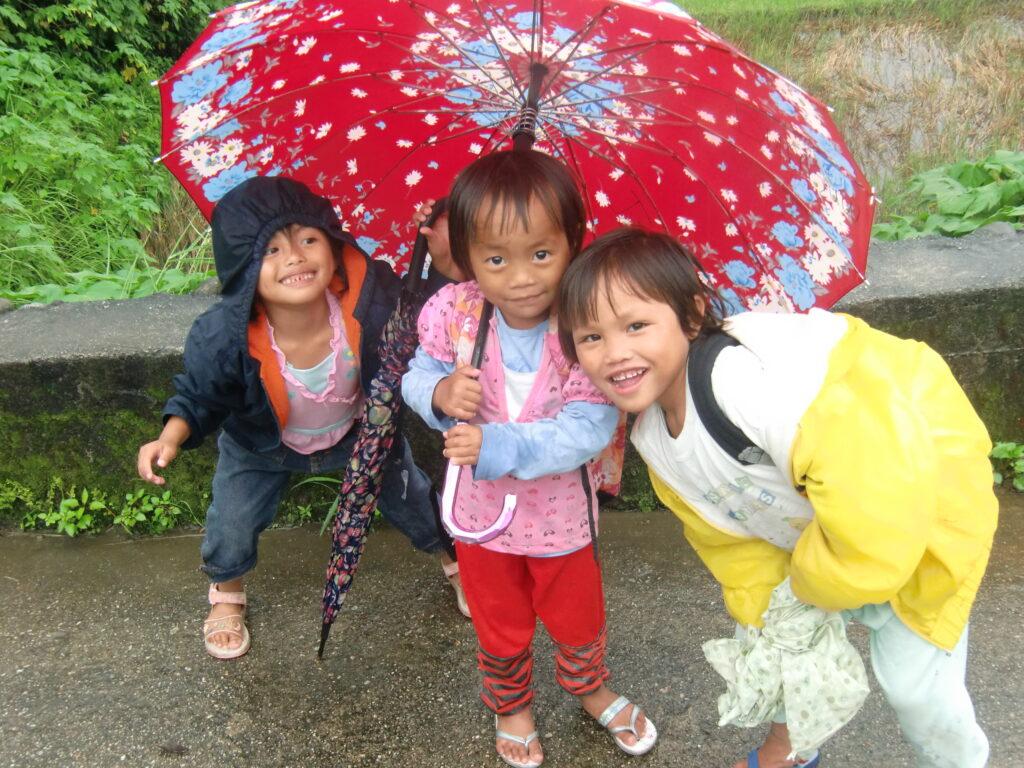 Three small children smile standing under a bright red umbrella