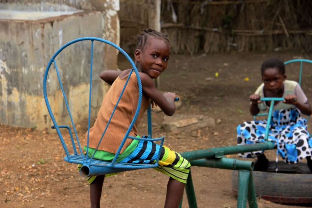 Two children play on a see saw