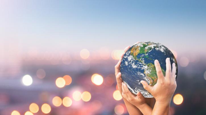 hands holding a globe above city lights