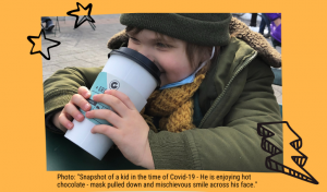 """Photo: """"Snapshot of a kid in the time of Covid-19 - He is enjoying hot chocolate - mask pulled down and mischievous smile across his face."""""""