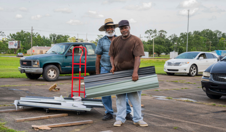 Pastor Harris of the Evergreen Missionary Baptist Church in DeQuincy, Louisiana and a volunteer help construct a shed during a bottled water and gift card giveaway to local residents still affected last year's Hurricane Laura and Hurricane Delta.