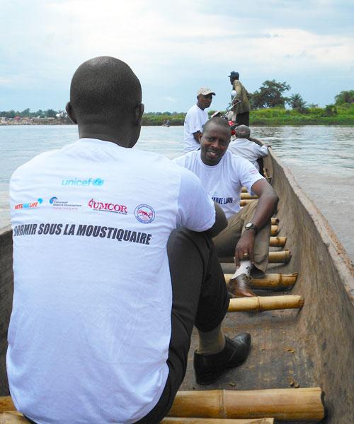 Malaria Control Agents cross Congo River in canoes